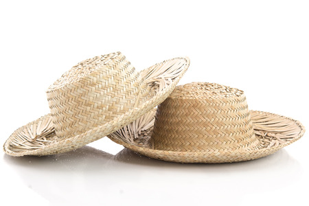 Close up of two vintage summer straw hats isolated on white background