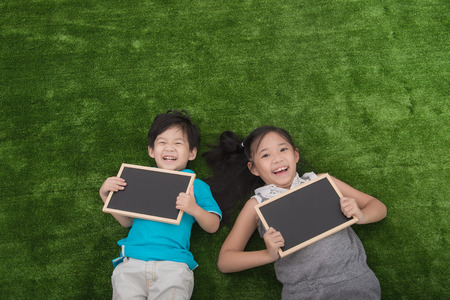 Cute asian children lying and holding blackboard on green grass