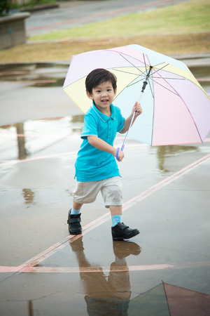fun day: Happy asian boy holding colorful umbrella playing in the park