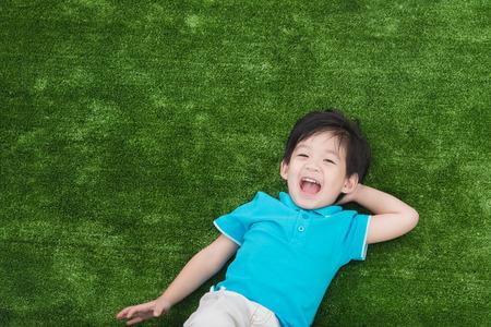 Leuk Aziatisch kind liggend op het groene gras