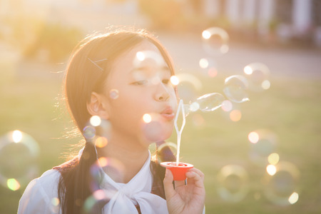light game: Cute asian girl is blowing a soap bubbles,vintage filter
