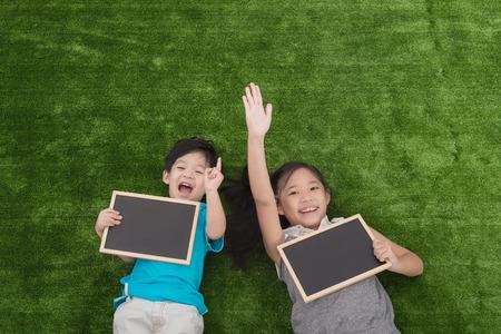 niños sonriendo: Niños asiáticos lindos que mienten y que sostiene la pizarra en la hierba verde