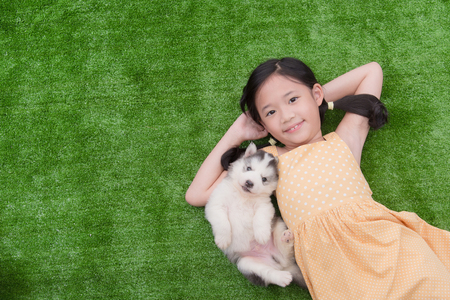 Cute asian girl lying with her puppy on green grass Zdjęcie Seryjne
