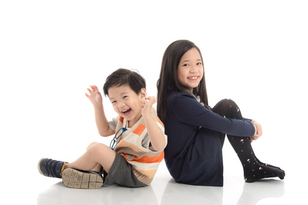 two girls hugging: Two  happy asian children sitting and leaning on each other ,white background isolated