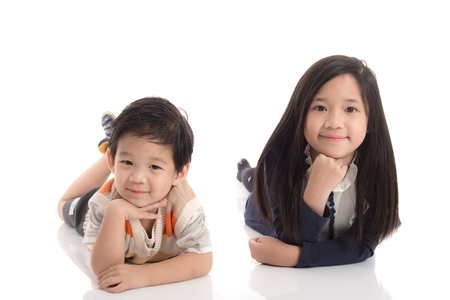 Two  happy asian children lying and leaning on each other ,white background isolated