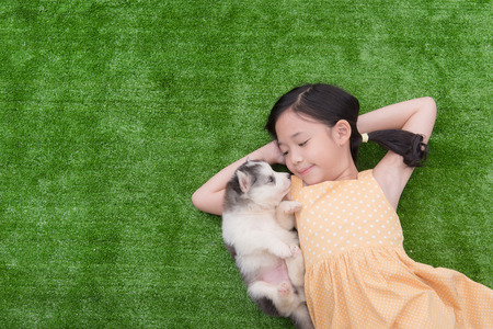 Cute asian girl lying with her puppy on green grass Stock Photo