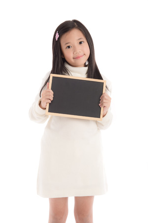 Cute asian girl in white turtleneck dress holding blackboard on white background isolated