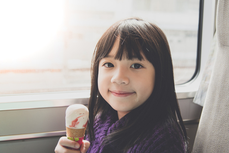Little asian girl smiling  and eating ice cream.She travels on a train,vintage filter Zdjęcie Seryjne