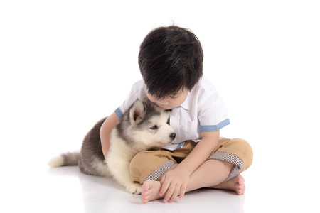 baby boys: Cute asian boy sitting with siberian husky puppy on white background isolated Stock Photo