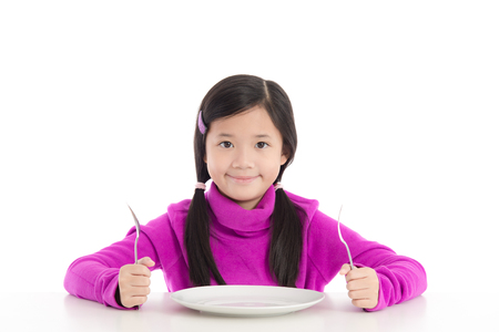 children eating: Beautiful asian girl holding a spoon and fork with empty white plate on white background isolated Stock Photo