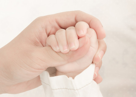 Concept of love and family. hands of mother holding baby'hand
