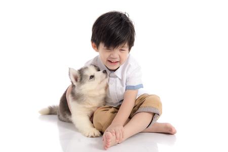 Leuke Aziatische jongenszitting met Siberisch schor puppy op witte geïsoleerde achtergrond