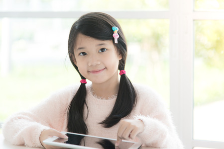 Beautiful asian girl using tablet on white table Zdjęcie Seryjne