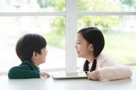 ni�os chinos: Retrato de felices los ni�os asi�tico con la tableta en blanco de mesa