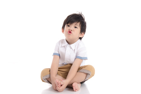 baby sit: Cute asian boy sitting on white background isolated Stock Photo