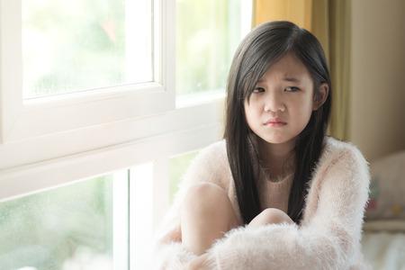 Portret van Aziatische mooie droevige meisje bij het venster, vintage filter