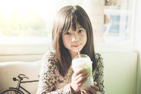 Mooi Aziatisch meisje die bevroren greentea, uitstekende filter drinken
