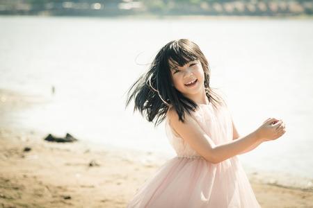 viaje familia: Muchacha asiática hermosa que sonríe en la playa, el filtro de la vendimia