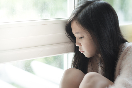 ethnic children: Portrait of asian beautiful sad girl at the window,vintage filter