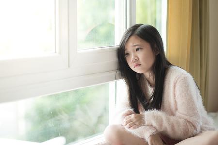 Portret van Aziatische mooie droevige meisje bij het venster, vintage filter Stockfoto
