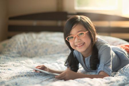 ベッドの上に横たわっている間タブレットを使用して美しいアジアの少女 写真素材