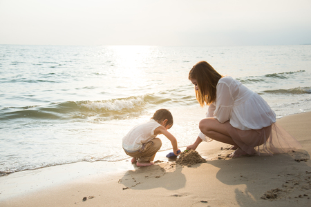 mother and son playing on the beach,vintage filter