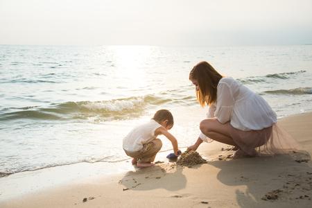 Mutter und Sohn spielen am Strand, vintage Filter