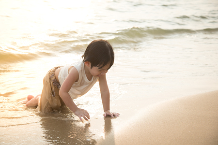 japan sky: Cute asian boy playing on the beach  at the sunset time