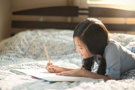 Muchacha asiática hermosa escribiendo a diario en la cama Foto de archivo - 47198792