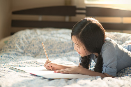 schreibkr u00c3 u00a4fte: Schöne asiatische Mädchen auf dem Bett Tagebuch Lizenzfreie Bilder