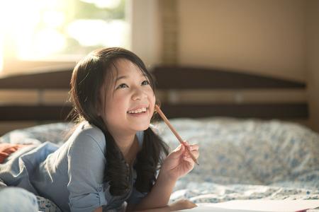 ベッドの上を考えて美しいアジアの少女 写真素材