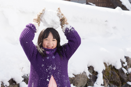 Cute asian girl smiling outdoors in snow on cold winter day