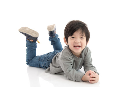Cute asian boy lying on white background isolated Stock Photo