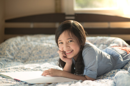 Happy asian girl reading a book on the bed,education concept Stock Photo