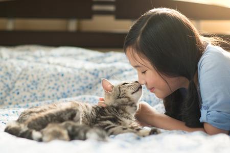 koty: Piękna dziewczyna azjatyckich całuje Amerykański krótkowłosy kot na łóżku