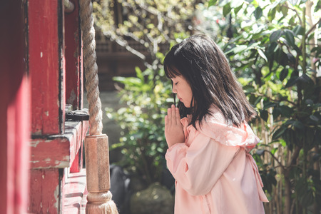 Beautiful asian girl is praying at the shrine,vintage filter