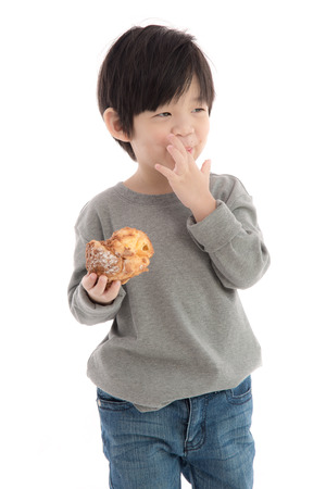 creampuff: Cute asian boy eating cream puff on white background isolated