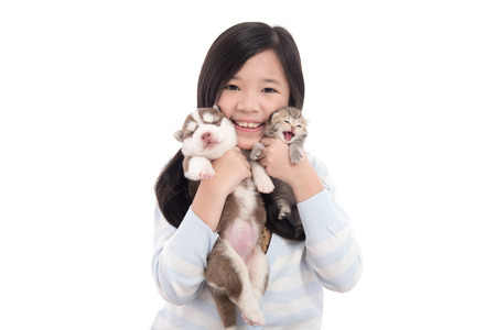 Beautiful asian girl holding newborn puppy and kitten on white background isolated