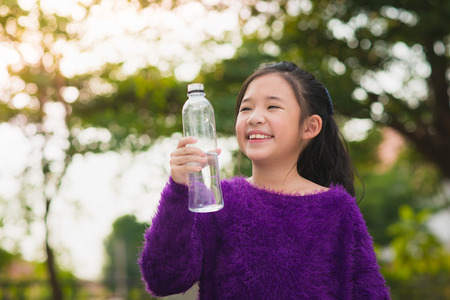 japanese children: Beautiful asian girl drinks water from a bottle outdoors Stock Photo