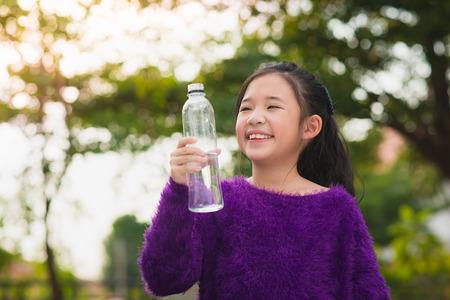tomando agua: Muchacha asiática hermosa bebe el agua de una botella al aire libre Foto de archivo