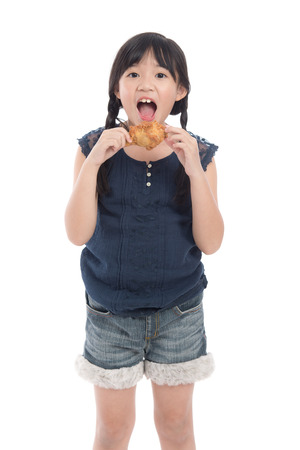 Cute asian girl eating fried chicken on white background isolated Stock Photo