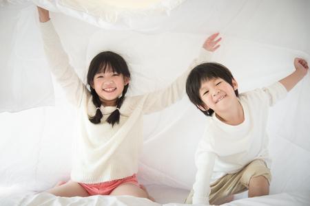 Niños asiáticos lindos que juegan bajo la manta en la cama blanca Foto de archivo - 49757152