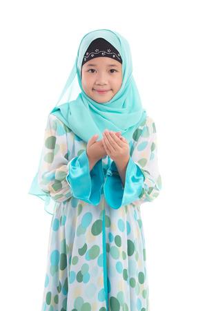 美しいアジアのイスラム教徒の少女の分離した白い背景上の祈り