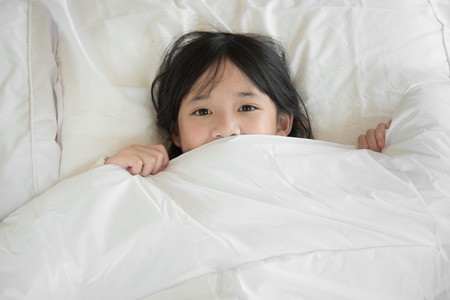 bed sheet: Cute asian girl lying under blanket on white bed Stock Photo