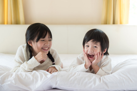 brother sister: Cute asian children lying on white bed