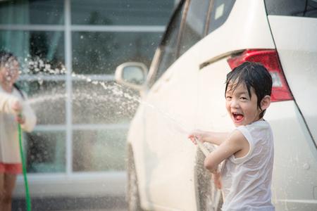 Aziatische kinderen wassen auto in de tuin