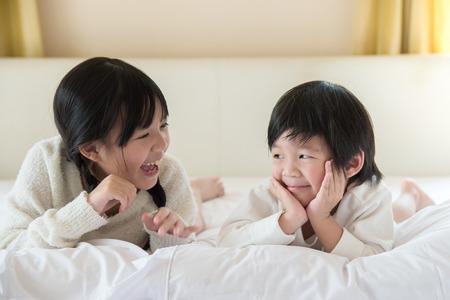 Leuke Aziatische kinderen die op wit bed liggen