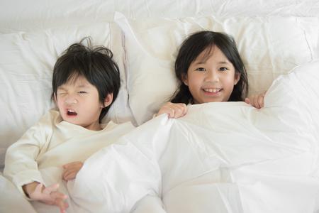 Leuke Aziatische kinderen spelen onder deken op witte bed