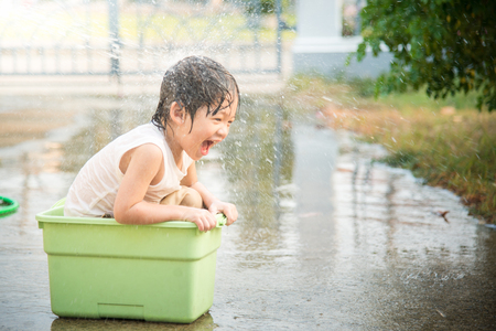 playing: Cute asian boy has fun playing in water from a hose