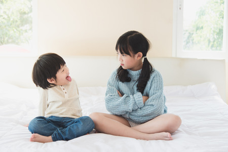 brother sister: Asian sister and brother quarreling on white bed